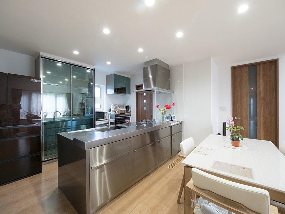 存在感のあるステンレス製キッチン、おしゃれなガラス戸のキッチン収納