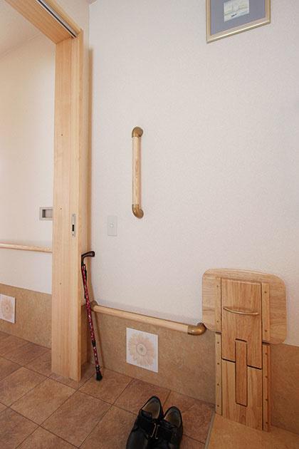 折りたたみができる玄関のベンチと、立ち上がりと移動の動作を補助するために施工した手すり