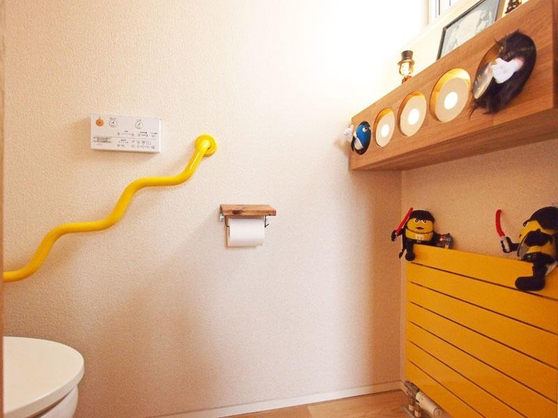 Sさんの要望で、トイレットペーパーを収納する棚を楽しい仕掛けにした(写真右上)。左の黄色い手すりは奇抜だが、実は実用性を考えたデザイン