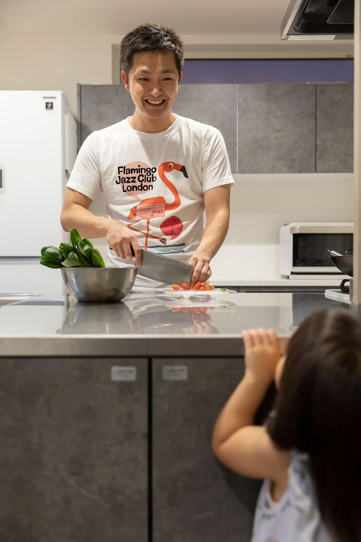 中華包丁を握るパパの料理姿を見つめる娘さん。