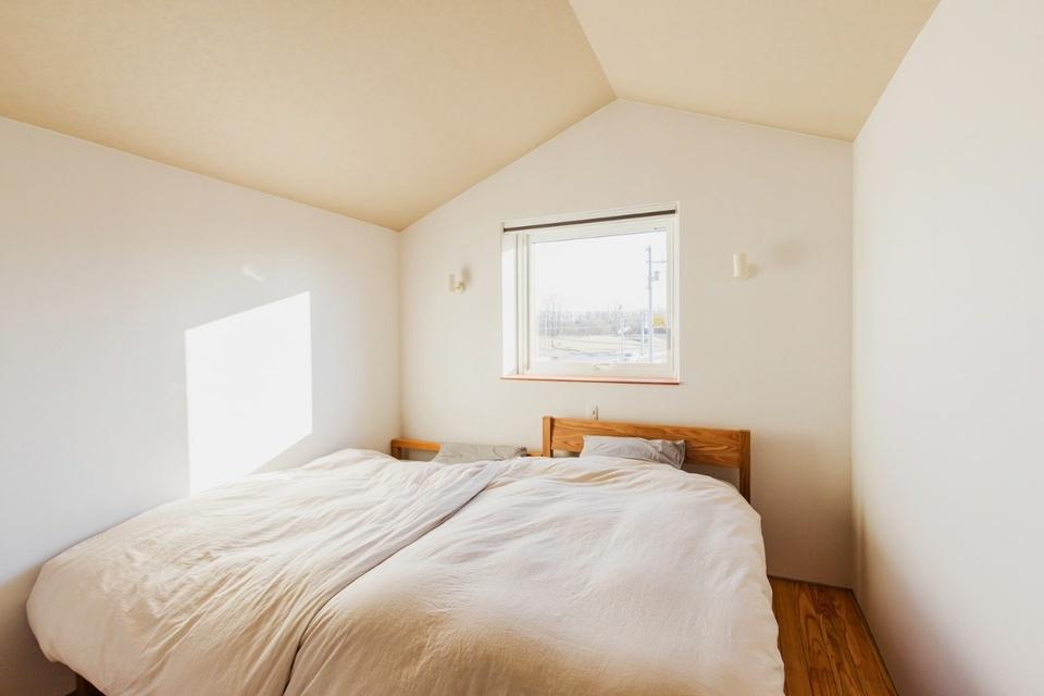 元の家の屋根を利用したという天井の形がユニークな2階の寝室