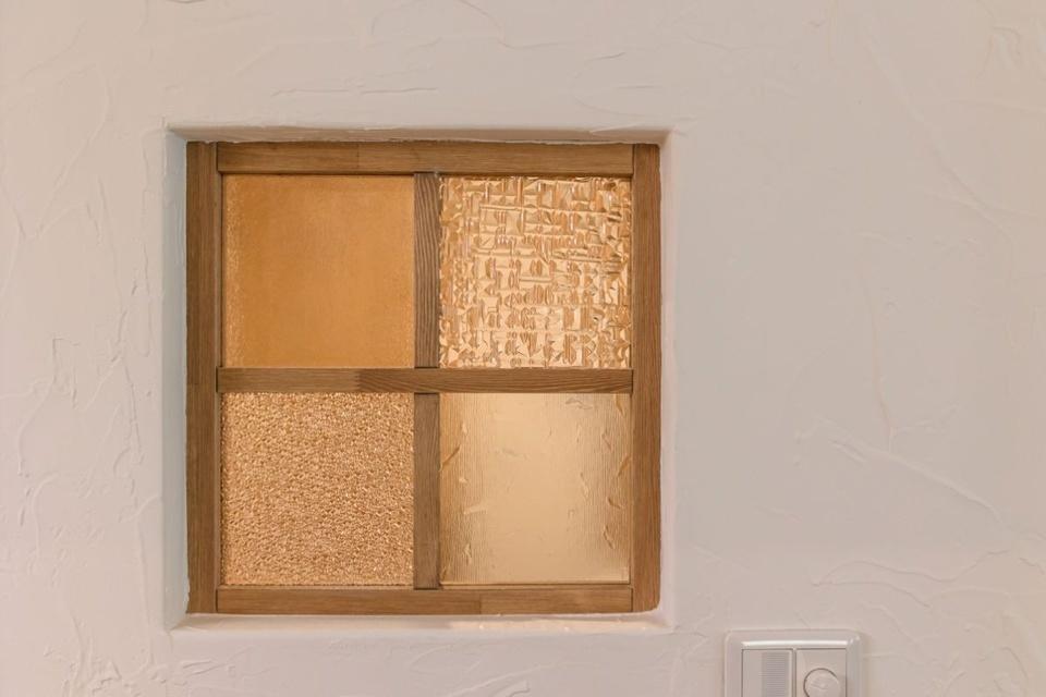乾燥室の窓。ガラスは数種ある候補の中からご夫婦で熟考して組み合わせました。塗り壁はカントリーヴィレッジの事務所と同じ、ざらりとした風合いを感じさせる仕上がりに